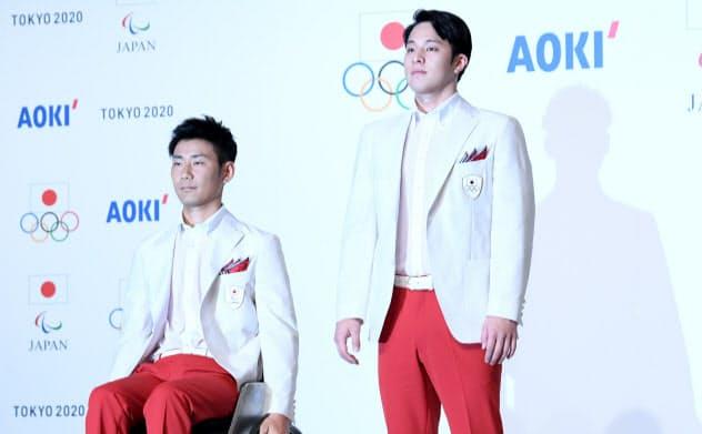 東京五輪・パラリンピックの日本代表選手団公式服を披露するパラアーチェリーの上山選手(左)と競泳の瀬戸選手(23日、東京都千代田区)