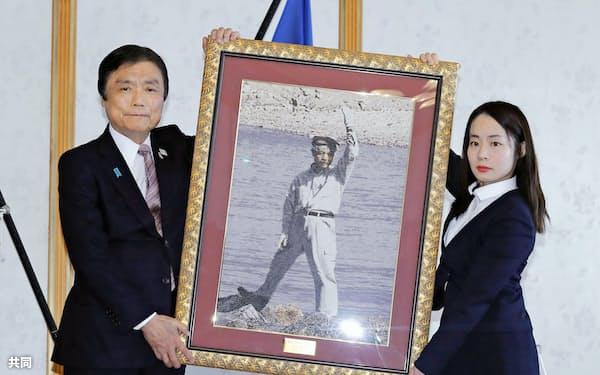 中村哲さんに県民栄誉賞が贈られ、福岡県の小川洋知事(左)から記念品を受け取る長女の秋子さん(24日午前、福岡県庁)=共同