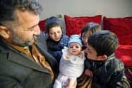 アフガニスタンの首都カブールで、ナカムラ・ムスリムヤールちゃん(中央)をあやす父サミウラさんと子どもたち(22日)=共同