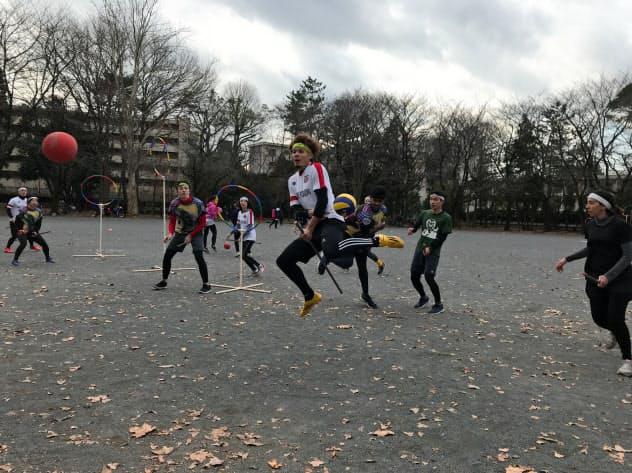 ホウキに見立てた棒などにまたがって競う(東京都品川区、写真中央が原田さん)
