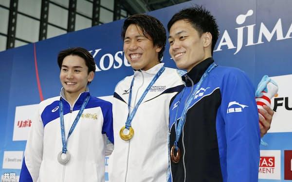 男子200メートル自由形で優勝し、笑顔の松元克央(中央)。左は2位の江原騎士、右は3位の坂田怜央(24日、東京辰巳国際水泳場)=共同