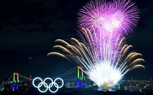 ライトアップされた五輪マークの後ろで記念花火が打ち上げられた(24日、東京都港区)