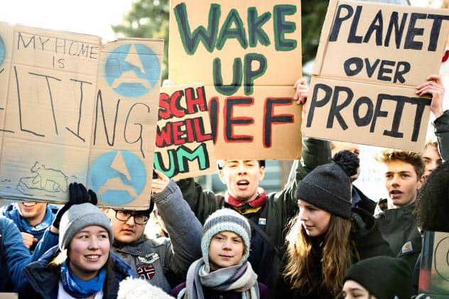 24日、ダボスで若者とデモ行進するスウェーデンの環境活動家、グレタ・トゥンベリさん(中央)=AP