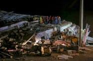 24日、トルコ東部で崩壊した建物で生存者の捜索に当たる救助当局者=ゲッティ共同)