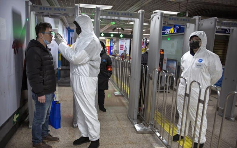 北京市内の地下鉄駅で乗客の体温を測る防護服姿の係員(26日)=AP