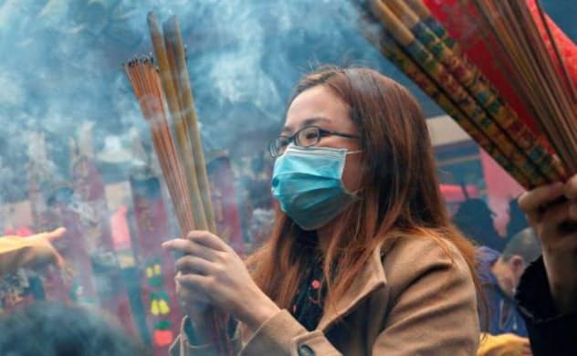 香港の寺院で旧正月に香をたく女性。香港は新型肺炎対策で緊急事態を宣言した=ロイター