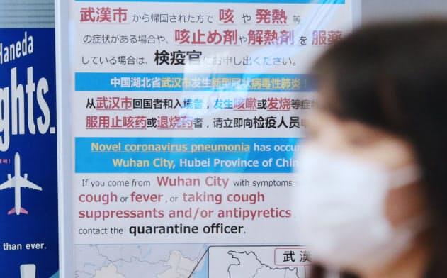 新型コロナウイルスによる肺炎について注意を呼びかける看板(27日午前、羽田空港国際線ターミナル)