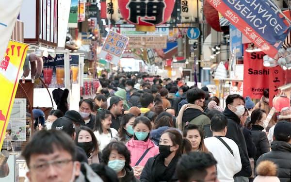 マスクをして買い物する観光客ら(27日、大阪市中央区の黒門市場)