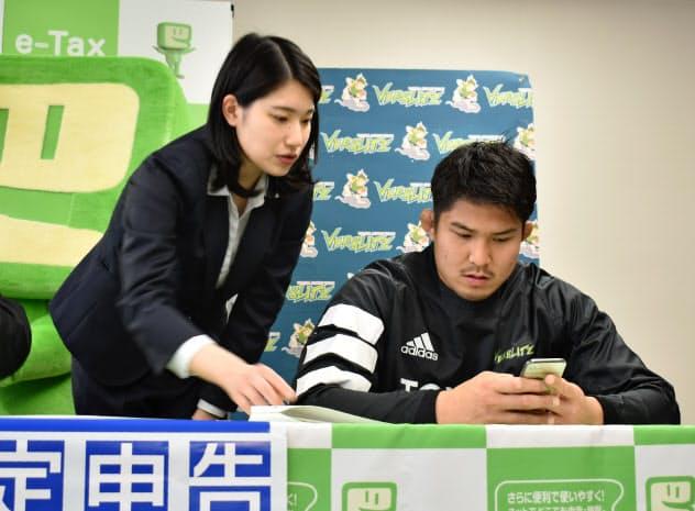 スマートフォンを使った確定申告を体験する、ラグビー日本代表の姫野和樹選手(27日、愛知県豊田市)