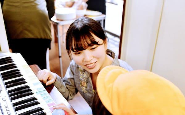 食事後に大学生ボランティア(中央)と遊ぶ子ども(大阪市西成区の「にしなり☆こども食堂」)
