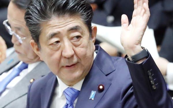 衆院予算委で答弁のため挙手する安倍首相(27日)