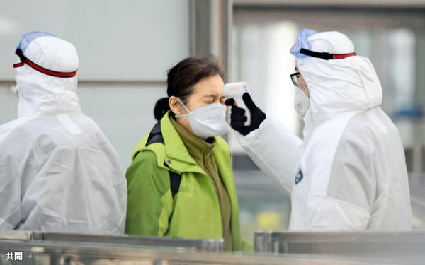 北京首都国際空港の鉄道駅の改札前で、防護服を着て乗客の体温検査をする担当者(27日)=共同