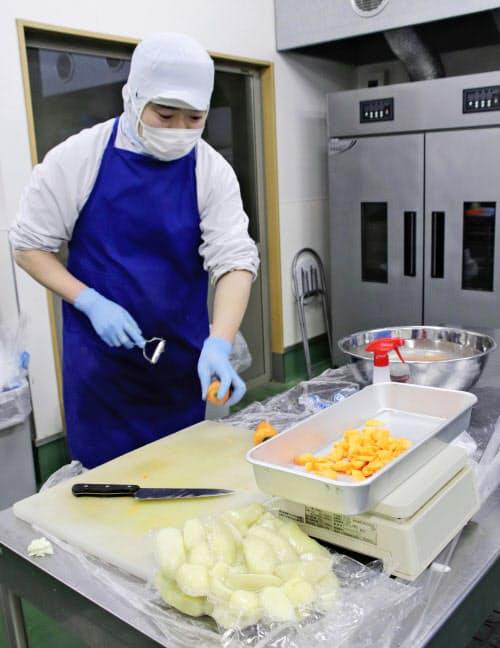 野菜を手際よく加工する障害者(2019年12月、北海道芽室町)=共同