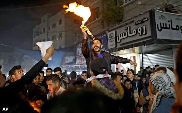 和平案に反発し、トランプ米大統領の写真に火を付ける人々(28日、パレスチナ自治区ガザ)=AP