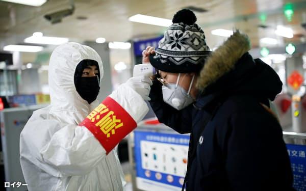 中国・北京の地下鉄駅で体温検査を受ける乗客(28日)=ロイター
