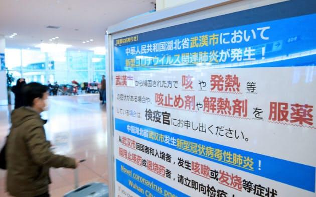 新型コロナウイルスによる肺炎について注意を呼びかける看板(27日、羽田空港国際線ターミナル)