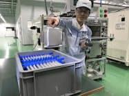 完成したリチウムイオンキャパシタを手に取る担当者(愛知県岡崎市)