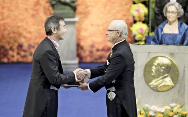 ノーベル賞授賞式で、スウェーデンのカール16世グスタフ国王(右)から物理学賞のメダルと賞状を受け取る梶田隆章・東大宇宙線研究所長=10日、ストックホルムのコンサートホール(共同)
