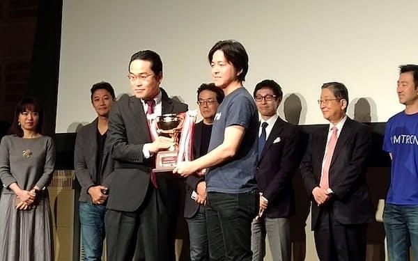 ファンズの藤田雄一郎社長(中央右)にトロフィーが手渡された