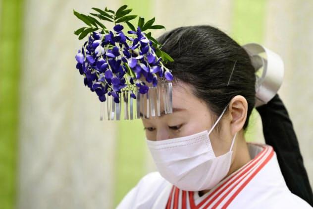 マスクをして参拝者に対応する春日大社のみこ(29日午後、奈良市)=共同
