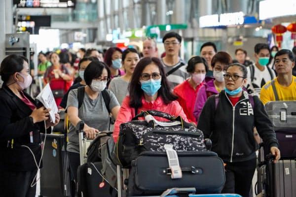 タイの空港ではマスク姿の旅行客が目立つ(25日、バンコク)