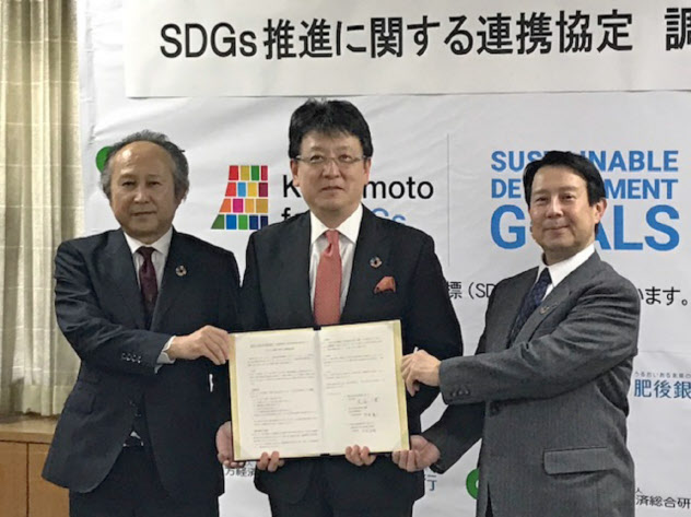 SDGs推進で連携協定を結んだ熊本市の大西一史市長(中)と肥後銀行の笠原頭取(右)ら(29日、熊本市役所)