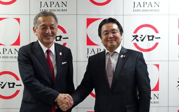 握手する2020年ドバイ国際博覧会陳列区域日本政府代表の中村富安氏(左)と、スシローの水留浩一社長
