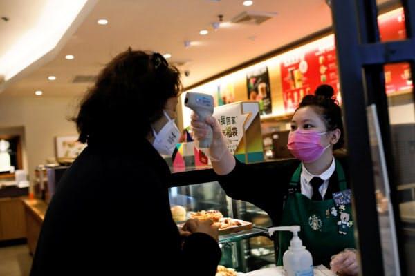 客の体温を測るコーヒー店員(30日、北京)=ロイター