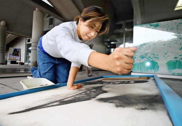 火山灰で桜島の噴煙や西郷隆盛を描く植村恭子さん(鹿児島市の桜島)