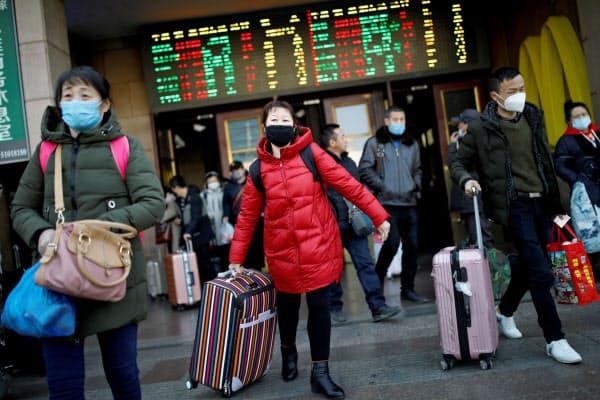 マスクを着用してスーツケースを運ぶ人々(30日、北京市)=ロイター