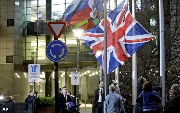31日夜、ブリュッセルの欧州議会前の英国旗を下げる関係者ら=AP