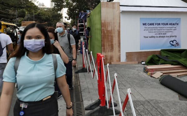 フィリピン政府は入国禁止措置を中国全土からに拡大した(マニラでマスク姿で歩く人たち)=AP