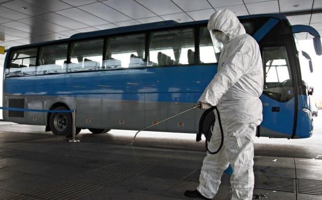 空港施設で消毒活動をする係員(1日、平壌)=AP