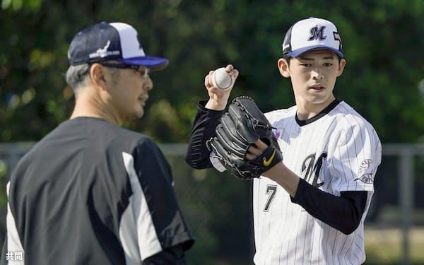 キャンプ初日、吉井コーチ(左)の指導を受ける佐々木朗=共同