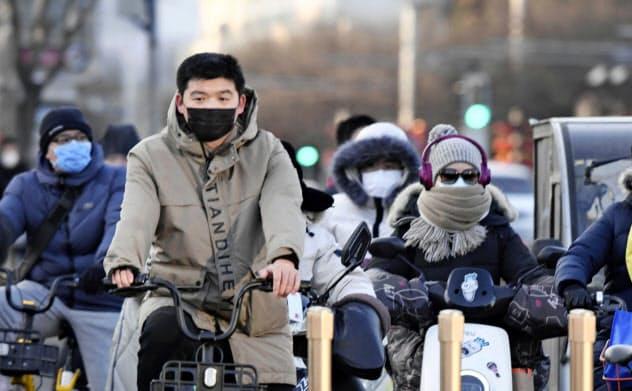 春節の大型連休が明け、マスク姿で行き交う北京市民ら(3日)=共同
