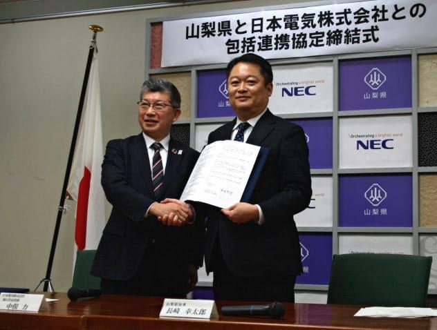 ローカル5Gなどの分野で協定書に調印したNECの中俣力執行役員常務(左)と山梨県の長崎幸太郎知事(3日、山梨県庁)