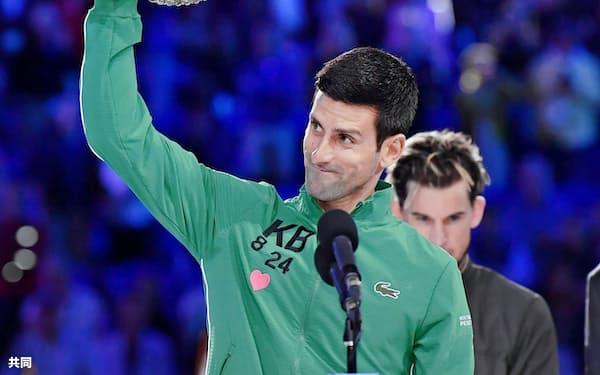 男子シングルスで優勝し、笑顔でトロフィーを掲げるノバク・ジョコビッチ=共同