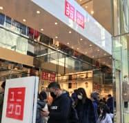 マスクを付けた外国人客が開店を待つ(29日、東京都中央区の「ユニクロ銀座店」)