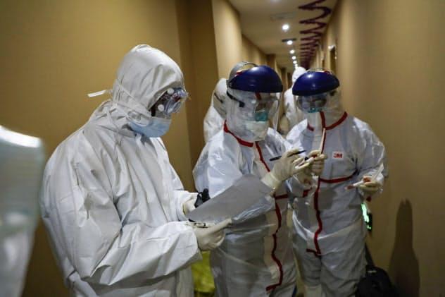 感染者の隔離施設として使われているホテルでウイルス検査をする医療従事者(4日、湖北省武漢市)=AP