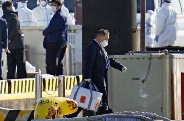 乗船者から採取した検体とみられる箱を運ぶ男性(5日午前、横浜港)=共同