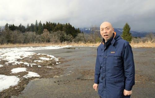 記録的な少雪で地肌が見える状態の貯雪場に立つ新潟県南魚沼市の関睦・創造主幹(1月24日)=共同
