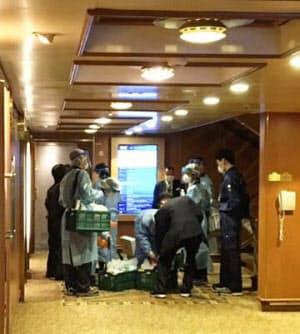 横浜・大黒ふ頭沖に停泊中のクルーズ船「ダイヤモンド・プリンセス」の船内で作業する検疫官とみられる担当者ら(4日未明)=乗客提供・共同
