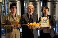 キリンHDの磯崎功典社長(中)の実家で収穫した温州ミカンを使いクラフトビールとして発売した