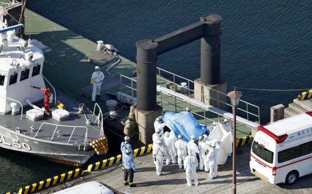クルーズ船「ダイヤモンド・プリンセス」内で新型コロナウイルスの陽性反応を示した乗船者を搬送する防護服姿の関係者=5日午前、横浜港