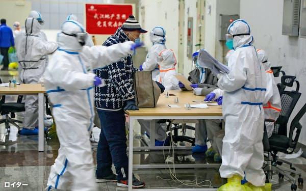 防護服に身を包む医療関係者(中国・武漢の展示会会場で)=ロイター