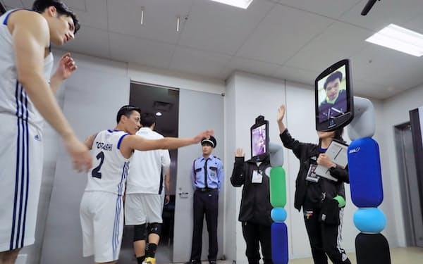 ハーフタイムで控室に向かう富樫勇樹選手らを出迎えるアバター(1月、札幌市の北海きたえーる)