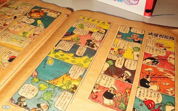 手塚治虫さんの遺品のスクラップ帳(手前)と「TEZUKA OSAMU EARLY WORKS」の2冊の見本=共同