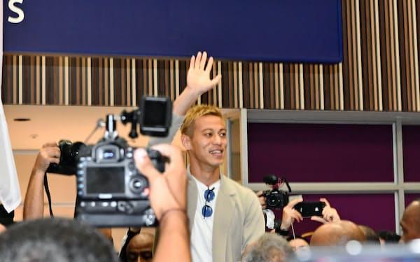 空港に到着し、サポーターに手を振る本田(7日、リオデジャネイロ)
