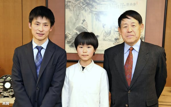 囲碁の女流特別採用試験で1位になり写真に納まる張心澄さん(中)。左は父親の張栩九段、右は祖父の小林光一名誉三冠(8日、東京都千代田区の日本棋院)=共同