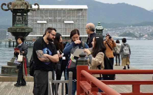 県立広島大学宮島学センターの学生は、厳島神社などを英語でガイドしている(広島県廿日市市)